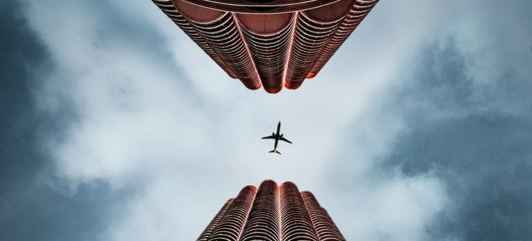 Airplane flying over twin buildings
