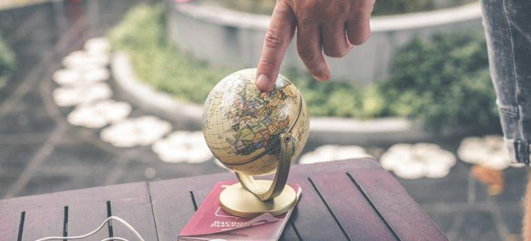 Person touching miniature globe on passport