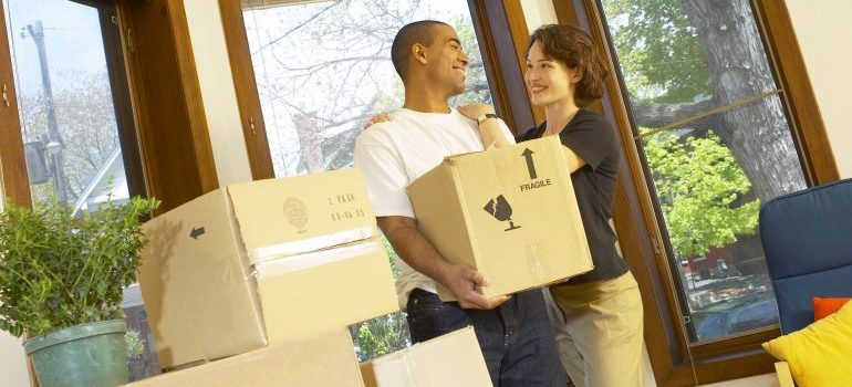 a couple standing among moving boxes
